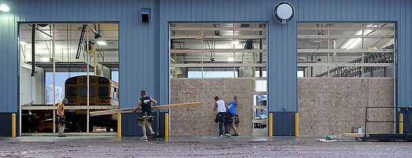 John Cross<br /> Workers put temporary panels up where high winds Thursday blew out three large overhead doors at North Central International on the west edge of New Ulm.