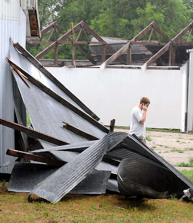 Nathan Schleeve talks on the phone as parts of the roof of his father Randy's machine shed lay on the ground on his farm along Le Sueur County Highway 112 Thursday. A storm Wednesday night brought straight-line winds through the area, knocking down trees and damaging buildings from Le Sueur to Le Center.