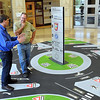 Pat Christman<br /> MnDOT's Giles Abbe answers questions about a roundabout from retired trucker Greg Schlenker while standing atop a model of the proposed roundabout at Madison Avenue and State Highway 22 Abbe created Tuesday at MnDOT's Mankato headquarters.