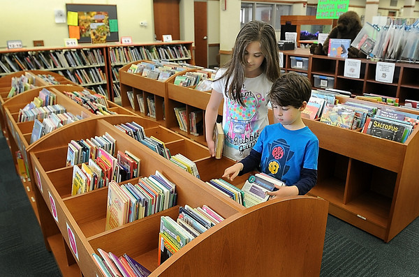 John Cross<br /> Alexa and Ryan Johnson peruse books in the North Mankato Taylor Library addition that was funded through sales tax proceeds.