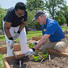 President of South Central College Annette Parker (left) and Brad Schloesser, Dean of the Southern Minnesota Center of Agriculture, plant a rosemary herb in the new community garden on the SCC campus on Thursday. Plans also include building a greenhouse at the site.  Photo by Jackson Forderer