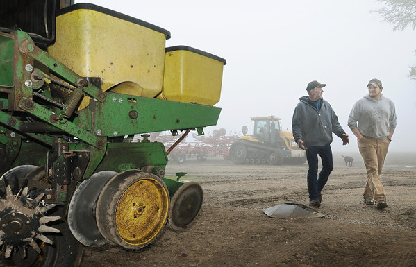Le Sueur County farmer Bob Braun (left) and farming partner Ryan Thelemann walk past a planter idled by wet weather. Photo by John Cross