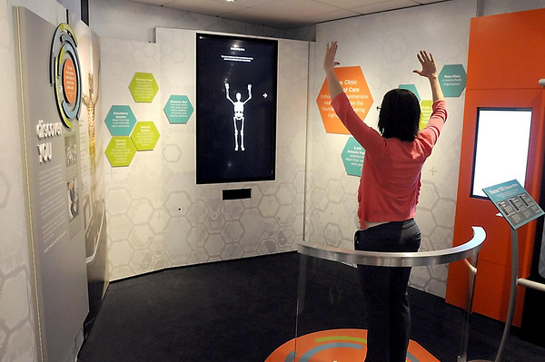 A visitor watches an image of a skeleton move in response to her movements in a mobile Mayo Clinic exhibit Wednesday at Madison East Center. The exhibit is part of Mayo's 150th anniversary.  Photo by Pat Christman