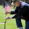 Norm Carlson of Mankato decorates his father's grave at Calvary Cemetery on Thursday. Photo by John Cross