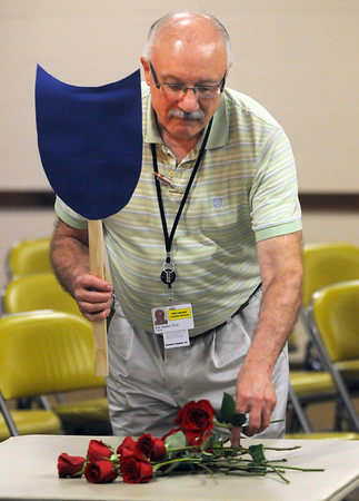 St. Peter Regional Treatment Center chaplain Bob Wieber places a rose on a table during a Remembering With Dignity ceremony Tuesday honoring those who were buried in the center's cemeteries. Each rose represents one of 12 unmarked graves that have been identified. Photo by Pat Christman
