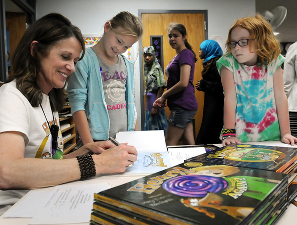 "Author Mary Blechwehl signs some of her books for Jefferson Elementary students Riley Jones (center) and Melisandra McLaughlin on Monday. The author of two popular children's books ""Henry! You're Late Again"" and ""Henry! You're Hungry Again?"" talked to students about the process of creating a book. Photo by John Cross"