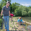 Dustin Demmer (left) places native Minnesota grasses along the shoreline of Lake Crystal on Friday. Dimmer and other volunteers planted 1,800 native plants to stabilize the shoreline of Lake Crystal. Photo by Jackson Forderer