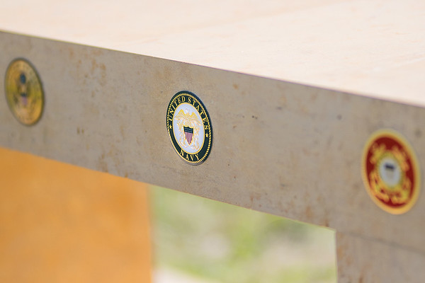 A veterans memorial bench at Kasota Hill Cemetery made by Connor Maday has the five emblems of the armed services on it. Maday has two great-grandfathers and one grandfather who served in the Navy. Photo by Jackson Forderer