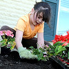 Emma Brewer, 8, plants flowers in a new planter on a patio outside the Minnesota Children's Museum Thursday.