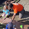 Reagan Sorenson, 7, gets some help laying patio bricks from Jeff Simonson.
