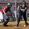 Mankato West catcher Kenzie Franke reaches for a bunt by Mankato East's Carolyn Osdoba that sticks in the soft dirt in front of home plate during their game Tuesday at Mankato West.