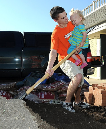 Jayda Becker, 2, is all smiles as she helps her father Micaiah shovel dirt for flower boxes at the Minnesota Children's Museum's patio.
