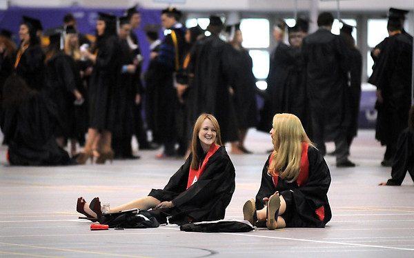 Pat Christman<br /> Minnesota State graduates Genevieve Simonson, left, and Deanna Gans relax before the start of the first of three commencement ceremonies Saturday at MSU's Myers Field House.