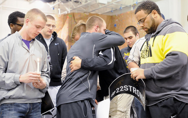 Members of the MSU football team comfort one another during a candle vigil for injured teammate Isaac Dallas Kolstad at Myers Field House on Sunday. Photo by John Cross