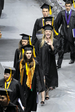 A graduate waves to friends and family during Saturday's ceremony. Photo by Pat Christman