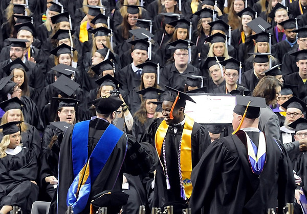 A graduate smiles as he collects his diploma during one of three commencement ceremonies Saturday at MSU's Taylor Center. Photo by Pat Christman