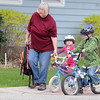 Sharon Jackson helps her grandchildren Lainey Lacher, 3, and Jackson Lacher, 7, with their bikes as they cross a street near Kennedy Elementary School Wednesday. Jackson rode his bicycle to school as part of Mankato Area PUblic Schools' Bike or Walk to School Day. Photo by Pat Christman