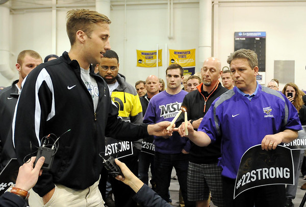 Minnesota State University, Mankato head football coach Todd Hoffner lights the candle of former team member Sam Thompson, who said a few words at a candle light vigil held Sunday night for MSU  player Isaac Dallas Kolstad, who is in critical condition. Police say he was assaulted early Sunday morning by former University of Minnesota quarterback Philip Nelson.