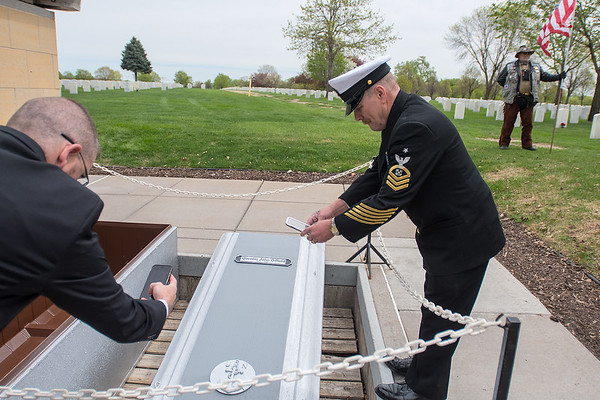 Carl Quentin Gifford Jr. (right) takes a picture of his great uncle Quentin Gifford's encasement at Fort Snelling Cemetery on Saturday. Gifford was buried with full military honors. Photo by Jackson Forderer