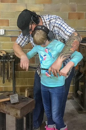 Tim Ericksen shows his daughter Nora, 10, how to bend metal into a small cowboy hat during a blacksmithing demonstration at Mankato Makerspace. Photo by Jackson Forderer