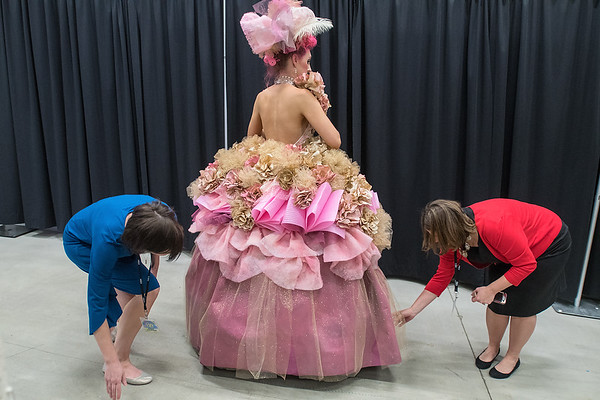 Julie Rudolph (left) and Ann Gustafson (right) tend to Kelsey Chester's dress backstage before the start of the RAW Fusion fashion show. Chester and her modeling partner Riley Weber won the people's choice award. Photo by Jackson Forderer