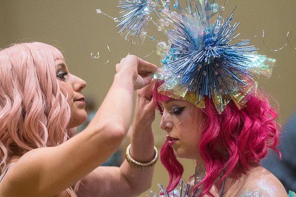 Melissa Ketchum puts some final touches on model Ellen Theis hair before taking the stage at RAW Fusion on Friday. Theis' outfit with Cambria used quartz, PVC piping and faux flowers. Photo by Jackson Forderer