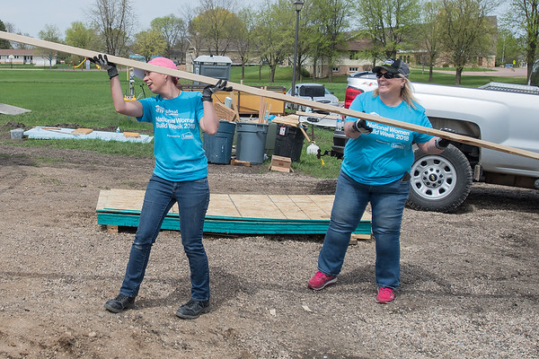 Charla Andrus (left) and Angie Kamin move a two by four at the Habitat for Humanity construction site in Nicollet on Thursday. A total of 19 women helped in the construction of a home during National Women Build Week. Photo by Jackson Forderer