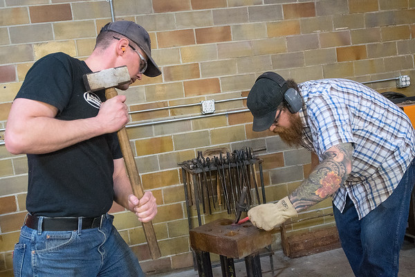 Martin Pansch (left) gets ready to hammer a piece of metal being held by Tim Ericksen as the two put on a blacksmithing demonstration at the Mankato Mankerspace. Pansch said he has been blacksmithing for 22 years and travels all over the state to do demos. The Mankato Makerspace is now outfitted for its members to make use of the blacksmith tools and studio. Photo by Jackson Forderer