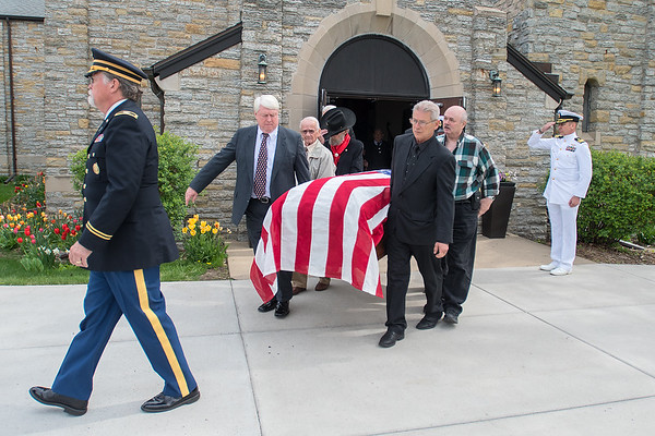 Being led by Rev. Dr. Kenneth Beale Jr., extended family members carry Quentin Gifford's casket out of Fort Snelling Chapel after Gifford's funeral on Saturday morning. At right, Gifford is saluted by Commander Brian Danielson, who would later play taps at Gifford's internment at Fort Snelling Cemetery. Photo by Jackson Forderer