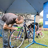 "Greg Lessard (left) performs a complimentary safety inspection on a bike belonging to a vistor of Key City Bike's grand opening at their new Vine Street headquarters Saturday. "" We're here now,"" Lessard said. ""We finally have a place to call home."" Photo by Casey Ek"