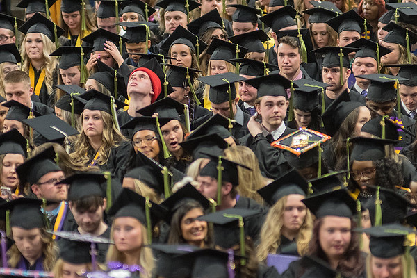 Blade Yocum (red hat) leans his head back as the long list of graduates names are announced for each person as they walk across stage to accept their degree at one of three commencement ceremonies held for Minnesota State University Students in Bresnan Arena on Saturday. Photo by Jackson Forderer