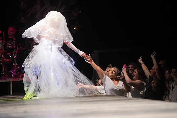 Fans shake Cloe Thelemann's hand as she walks off of the runway at the Raw Fusion fashion show. Thelemann dressed as Madonna's Material Girl for American Way Realty. Photo by Jackson Forderer