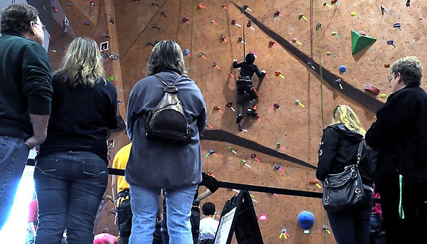 People watch a boy scale the climbing wall in MSU's Myers Field House Saturday.