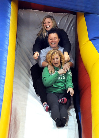 From front, Janessa Burch, Jenny Schulz and MSU student Jaida Burch show off for their parents by going down an inflated slide during MSU Family Weekend's carnival Saturday at Myers Field House.