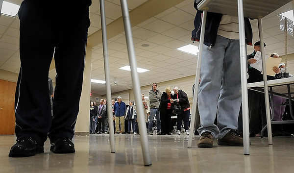 John Cross<br /> Voters in Ward 10, Precinct 4 at St, John's Catholic Church wait in line Tuesday. At noon, the line of voters stretched across the room, up a stairway and a hallway all the way to the entance of the building.
