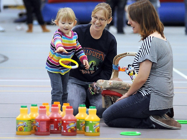 Residence Hall Assocation's Andrea Polleys (right) and April Hornemann watch April's daughter Kendra, 3 toss a ring at juice containers during MSU's Family Weekend carnival Saturday at Myers Field House.