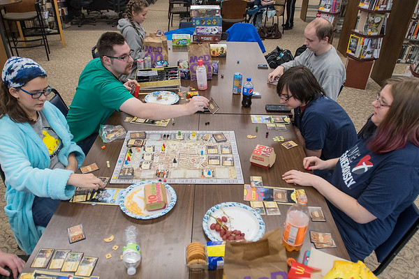 Adam Tillson (second from left) draws a card while playing Lords of Waterdeep, a Dungeon and Dragons board game, with Logan Krevchuck (second from right), 15, Alissa Wolf (right), 17, and Samantha Kopecky (left), 12, at the Waseca Library on Saturday. A group of gamers gathered to play video and board games for 25 hours to raise money for Extra Life which benefits the Children's Miracle Network. Photo by Jackson Forderer