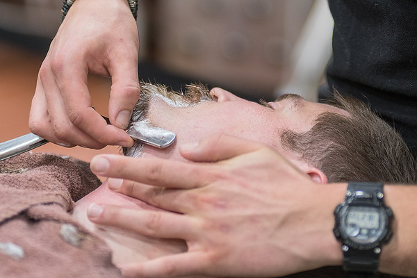 Logan Woods of Y Barbers gives a shave to Hunter Wolf at the Grow Mankato event held at Mankato Brewery on Thursday. Photo by Jackson Forderer