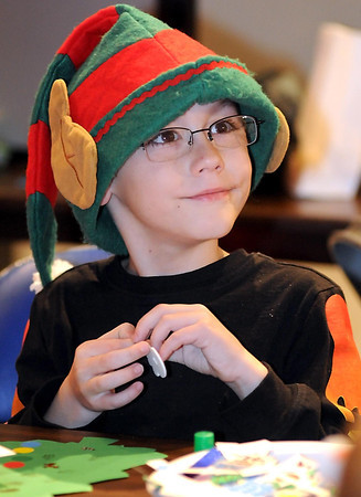 Alex Strand, 7, is dressed for the season as he decorates a Christmas card at the Southern Minnesota Christmas Festival Friday at the Verizon Wireless Center.