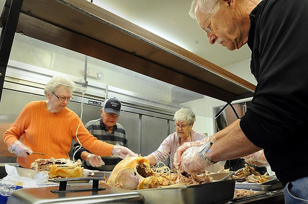 John Cross<br /> From left, Marilyn Drysdale, Clair Meredith, Janice Fredericksen and Ralph Meredith prepare roast turkeys Tuesday that willl be served Thanksgiving Day at the First Presbyterian Church in Lake Crystal. Reservations for the meal that will be served from 11 a.m. to 1 p.m. are recommended and can be made by calling 726-2877.