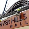 Workers place the last piece atop a new sign in front of River Hills Mall Wednesday afternoon.