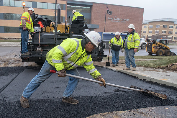 Joe Menjavar uses a rake to flatten asphalt in a driveway adjacent to Fifth Street on Tuesday. Photo by Jackson Forderer