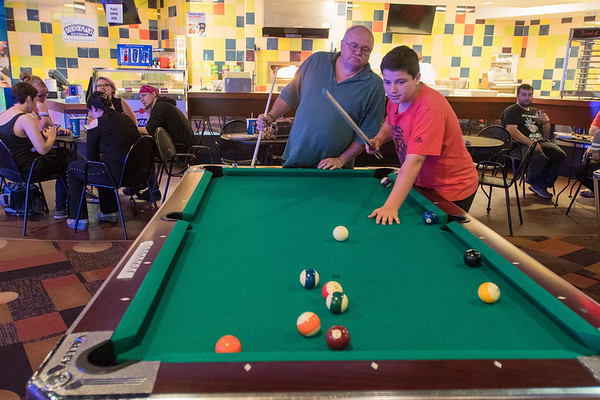 Ron Stanley looks over his 13-year old son's Brian Stanley's shoulder as the two played pool at the Wow! Zone  on a Saturday evening. Photo by Jackson Forderer