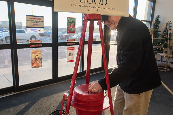 Harry Popiel puts a donation into the Salvation Army red kettle on his way out of Hobby Lobby on Thursday. Photo by Jackson Forderer