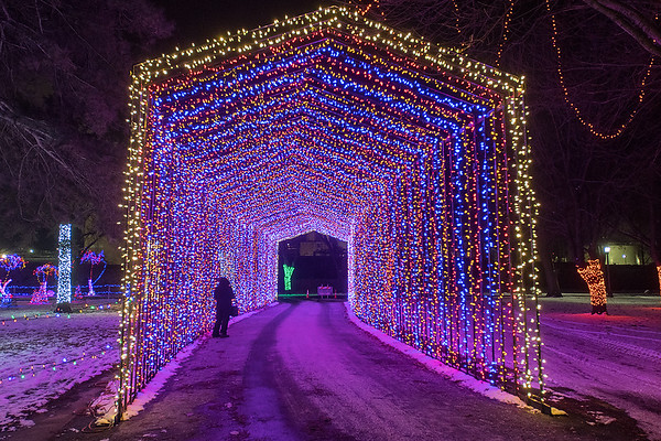 A pedestrian walks through the light tunnel for cars at Kiwanis Holiday Lights in Sibley Park on Tuesday. The event includes three LED Christmas trees that can be programmed to various patterns. Kiwanis Holiday Lights president Scott Wojcik said that there are 1.7 million lights in the park. Photo by Jackson Forderer