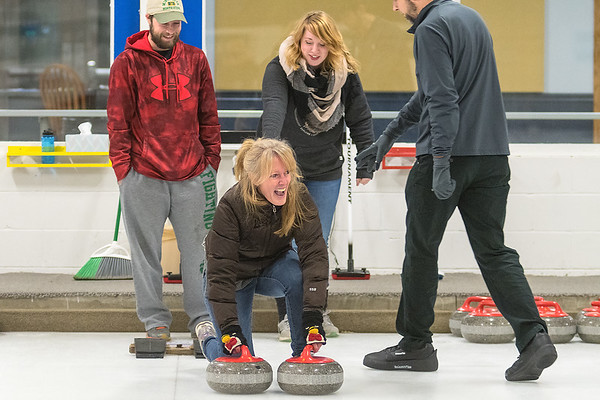 Kelly Knott (center) has a good laugh at herself along with Matt Ohman (upper left) and Kallen Knott (upper center) as Knott tried to maintain her balance while learning to curl at the Mankato Curling Club on Friday. Joe Gangi (right) led an introductory session to curling for newcomers interested in curling. Photo by Jackson Forderer