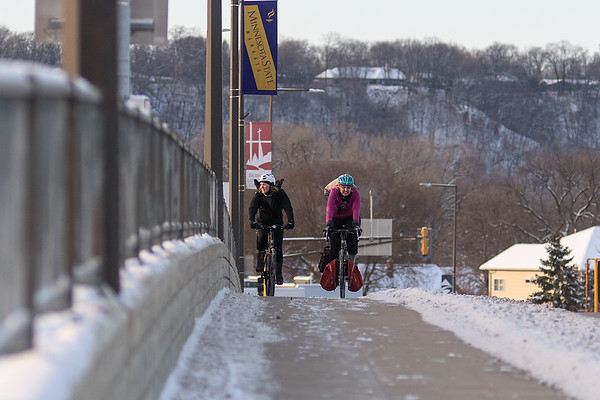 Jessica Myer (right) and Jacqueline Karsten (left) cross Veteran's Memorial Bridge from North Mankato to Mankato after going to Arizone Olive Oil Co., one of eight possible stops for the Cranksgiving alley cat. Photo by Jackson Forderer