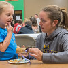 Bailey Rohrich (left), 4, licks peanut butter off of her fingers after covering a toilet paper roll with it while making a bird feeder with her mom Beth Rohrich at Epiphany Church in Eagle Lake during the benefit Turkeys, Pins and TP. Organizer Jan Lange said that at least 650 rolls of toilet paper were donated for local area homeless. Photo by Jackson Forderer