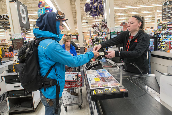 Peter Woitas (left) gets his change from a Cub Foods cashier after purchasing food products as he raced in Key City Bike's second annual Cranksgiving alley cat bike rice, which benefitted the Committee Against Domestic Abuse. Participants could go to eight different grocers and purchase food that would score them points at the end of the race. Photo by Jackson Forderer
