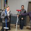 Suzie Gangi hands out brooms to newcomers at the Mankato Curling Club during an introductory training session on Friday. Photo by Jackson Forderer